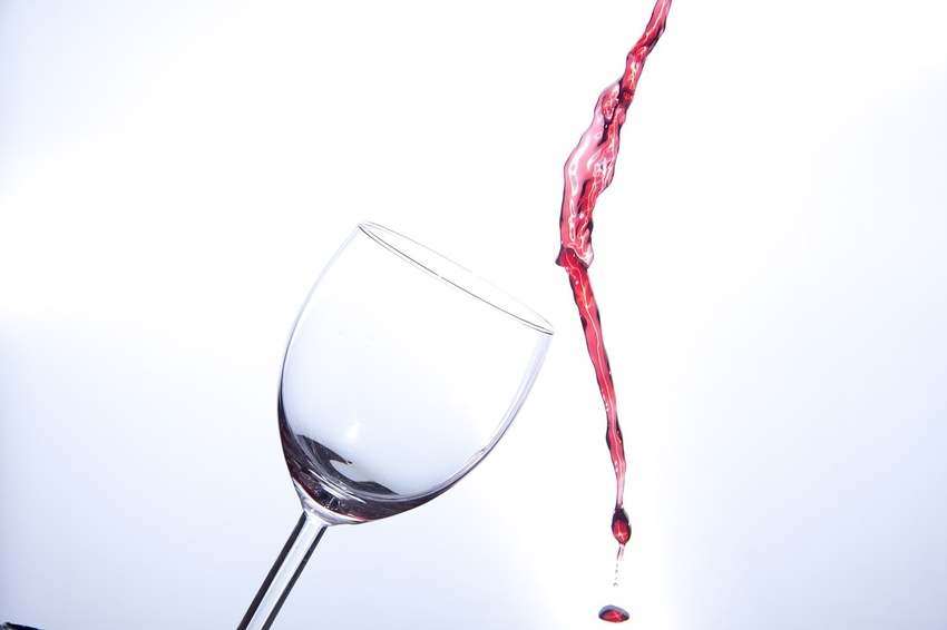 Wine pouring past empty glass onto carpeting below