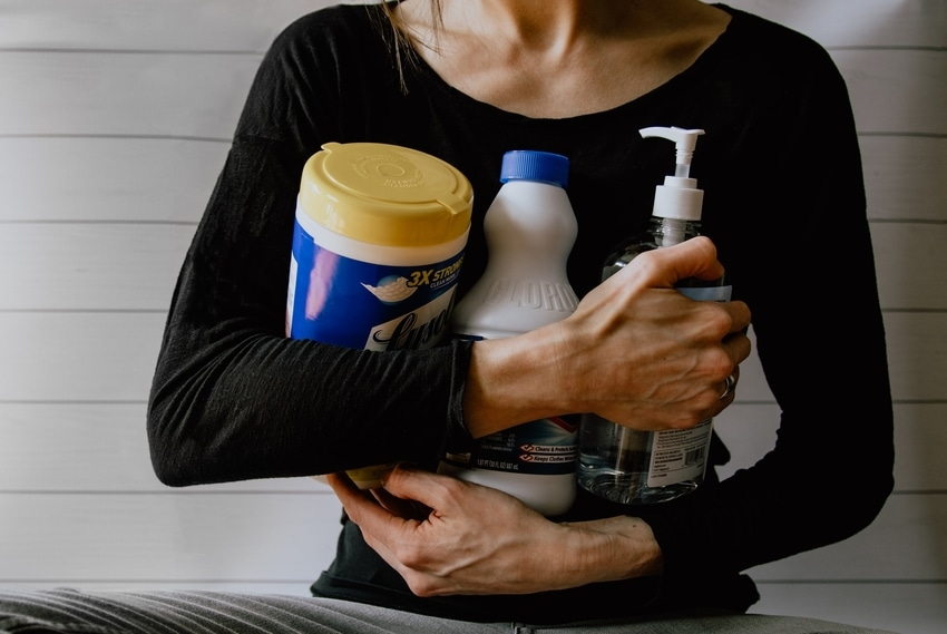 Woman in black long-sleeved shirt clutching cleaning products to chest before attempting DIY carpet stain removal