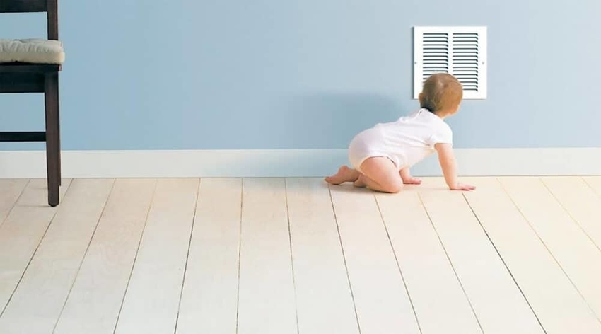 Crawling baby in diaper peering into air duct vent