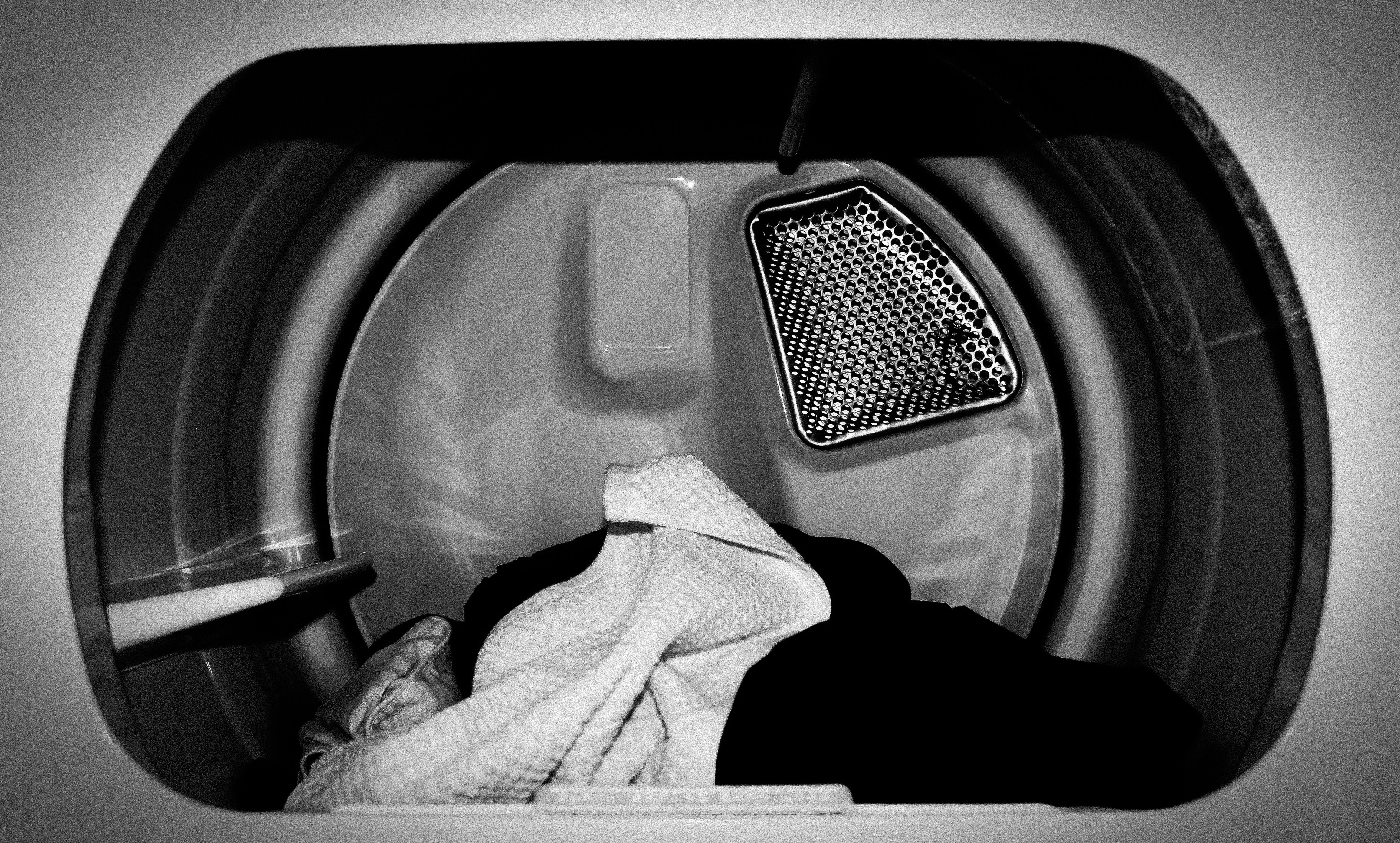 Black and white close-up view of clothes dryer's interior with clothing inside