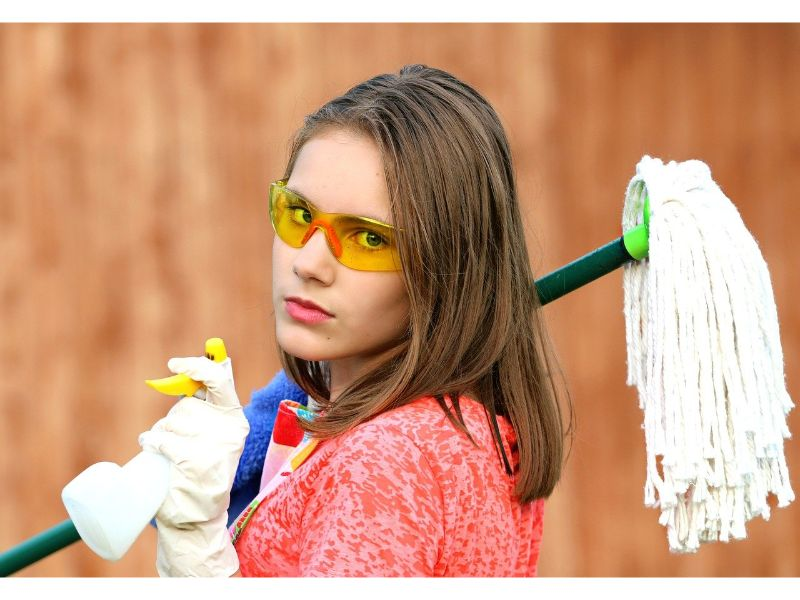 Woman in goggles and apron facing camera holding spray bottle, rag and mop for DIY home cleaning